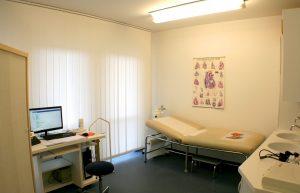 Behandlungsraum mit Liege und Schreibtisch
